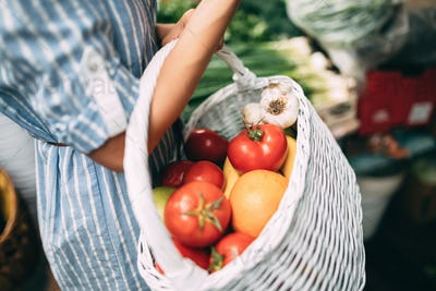 Close-up view of woman's basket full of groceries