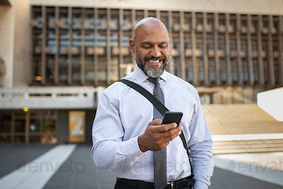 Happy formal businessman using phone on street