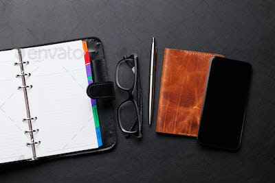 Office workplace table with supplies and smartphone