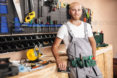 Smiling foreman in work clothes holding stapler in hand dreamily