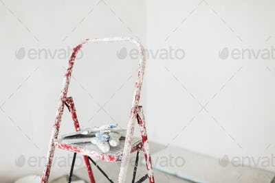 Close up ladder with putty knives over white background isolated