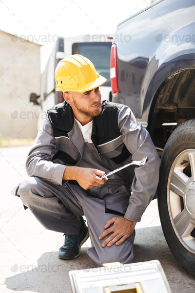 Young mechanic in work clothes and yellow hardhat thoughtfully l