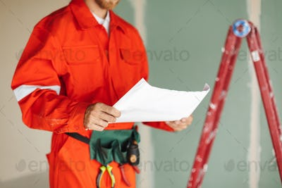 Close up foreman in orange work clothes and yellow hardhat holdi