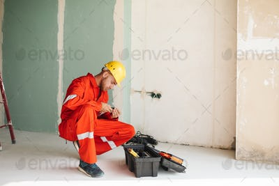 Foreman in orange work clothes and yellow hardhat thoughtfully c