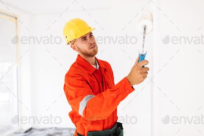 Thoughtful foreman in work clothes and yellow hardhat using pain