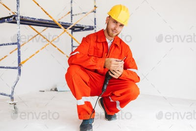 Young smiling builder in orange work clothes and yellow hardhat