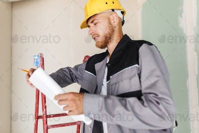 Engineer in work clothes and yellow hardhat dreamily looking on