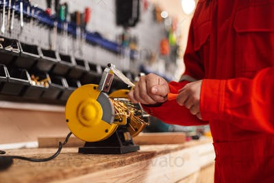 Close up builder using knife sharpener in workshop isolated