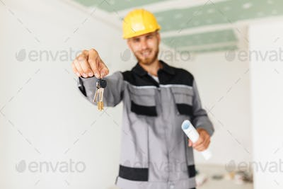 Close up engineer in work clothes and yellow hardhat happily hol