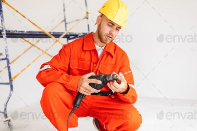 Builder in orange work clothes and hardhat thoughtfully using el