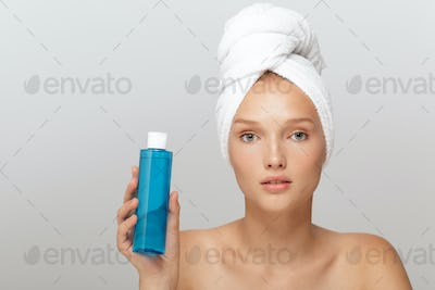 Portrait of young beautiful woman without makeup with white towe