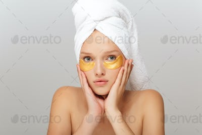 Portrait of young woman with white towel on head without makeup