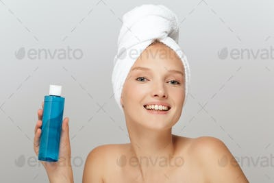 Portrait of smiling girl without makeup with white towel on head