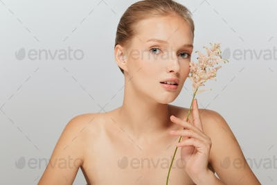 Portrait of young pensive lady without makeup holding beautiful
