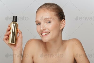 Portrait of young pretty woman without makeup holding cosmetic b