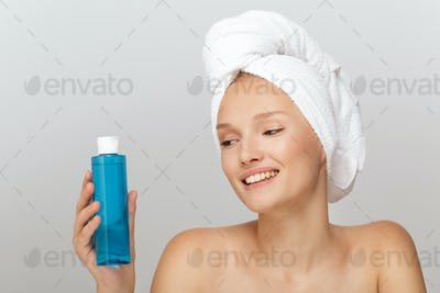 Portrait of cheerful girl without makeup with white towel on hea