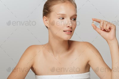 Portrait of pretty girl without makeup holding little capsule pi