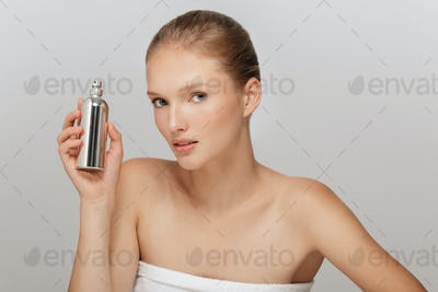 Portrait of beautiful girl without makeup holding perfume bottle