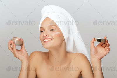 Portrait of young joyful woman with white towel on head without