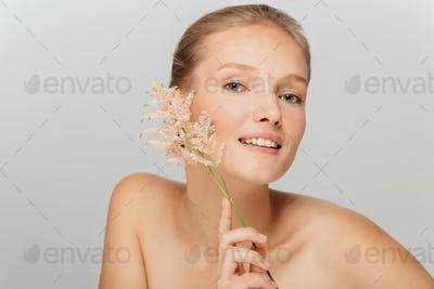 Portrait of young smiling lady without makeup holding beautiful