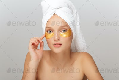Portrait of young attractive woman with white towel on head with