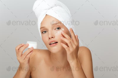 Portrait of young pensive woman without makeup with white towel