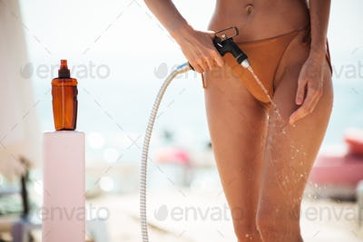 Photo of young woman body rinsing beach sand off her legs on beach