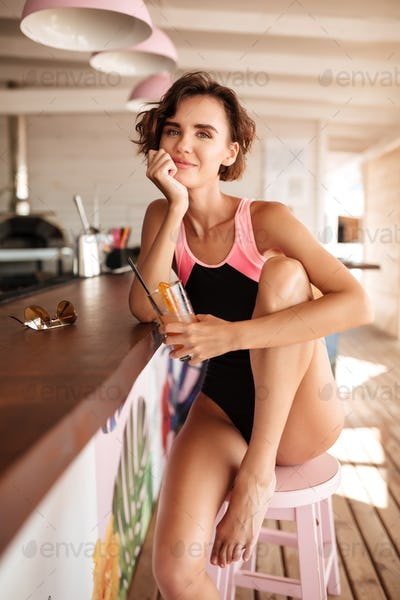 Portrait of beautiful lady in trendy swimsuit sitting at bar counter with cocktail in hand