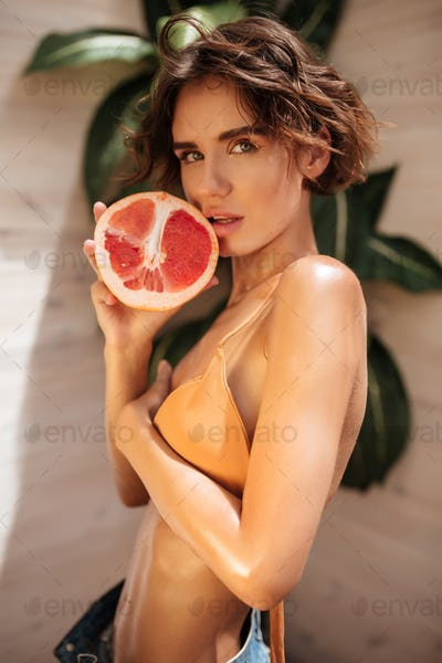 Young nice girl standing with grapefruit on wood background