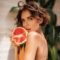 Girl in beige bikini and denim shorts thoughtfully looking in camera with half of grapefruit