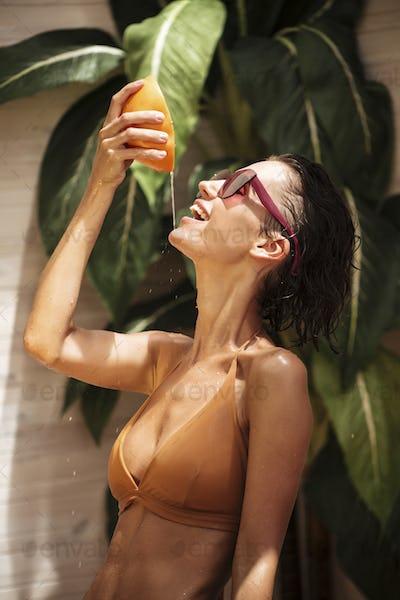 Portrait of joyful girl in beige bikini and sunglasses standing and squeezing grapefruit juice