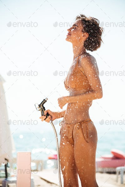 Young lady in beige swimsuit rinsing beach sand off her body on beach