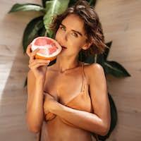 Portrait of beautiful girl in beige bikini thoughtfully looking in camera with half of grapefruit