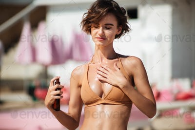Portrait of young happy girl in bikini standing on the beach and using body oil