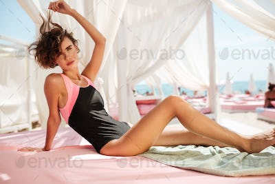 Beautiful girl in trendy swimsuit sitting in beach tent and thoughtfully looking in camera