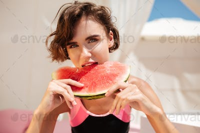 Girl in trendy swimsuit sitting in beach tent and dreamily looking in camera while eating watermelon