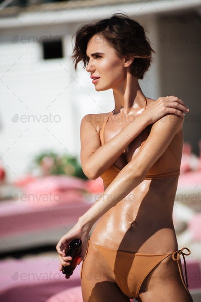 Young girl in bikini standing on the beach and thoughtfully looking aside while using body oil
