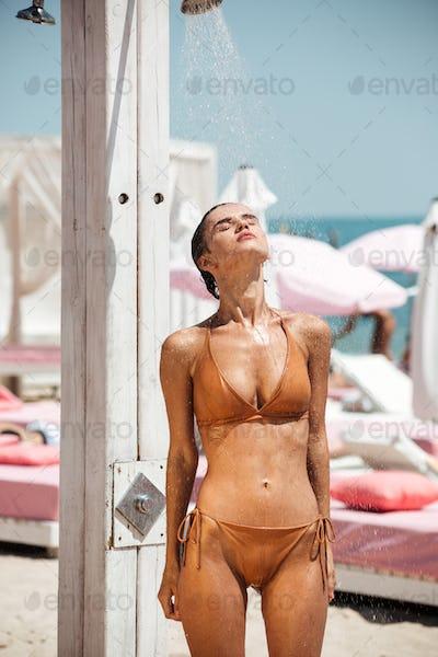 Beautiful pensive girl in beige bikini dreamily closing her eyes while taking shower on the beach
