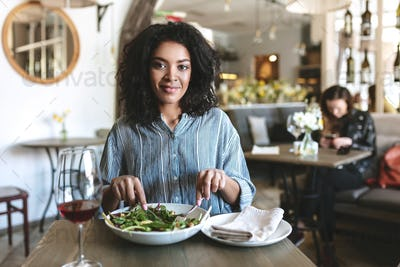 Young girl with dark curly hair eating salad and drinking red wine at cafe