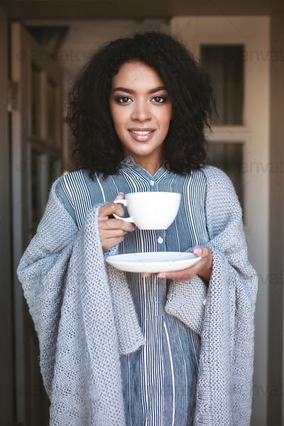 Portrait of smiling African American girl wrapped in plaid with cup of coffee in hands