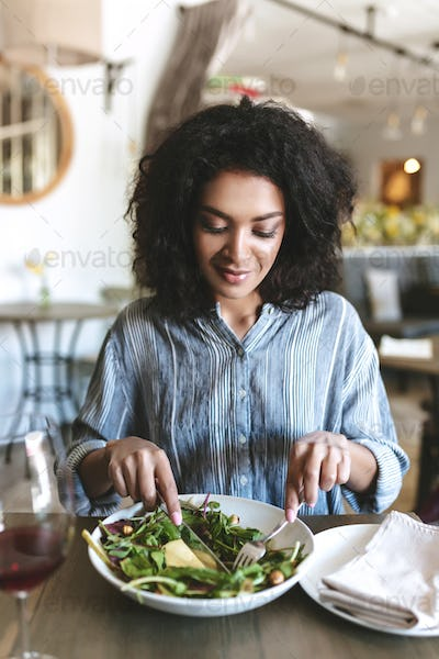 Smiling girl with dark curly hair sitting in restaurant with glass of red wine and salad on table