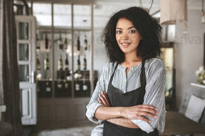 Portrait of beautiful African American girl wearing shirt and apron in restaurant