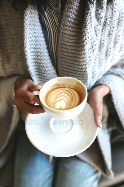 Young woman hands holding cup of coffee and saucer Woman hands with cappuccino in white cup