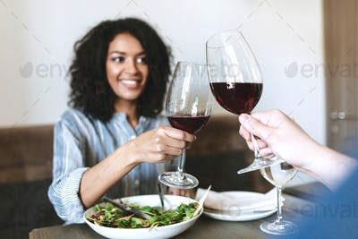 Pretty African American girl eating salad and drinking wine in restaurant