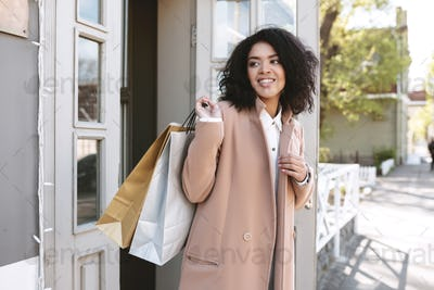 Pretty smiling girl in beige coat standing with packets in hand
