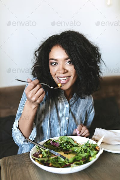 Portrait of smiling lady with dark curly hair and salad on table at cafe