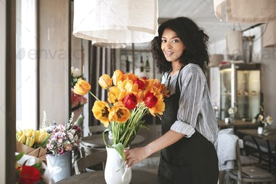 Beautiful florist in apron creating big bouquet of colorful tulips in vase