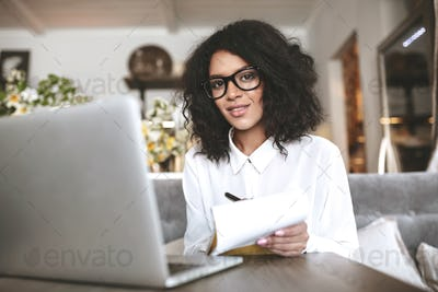 Young African American girl sitting at cafe with laptop and notebook in hand