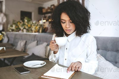 Young girl sitting in restaurant with cup of coffee in hand and thoughtfully looking at menu