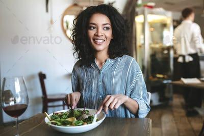 Nice African American girl with dark curly hair eating in restaurant